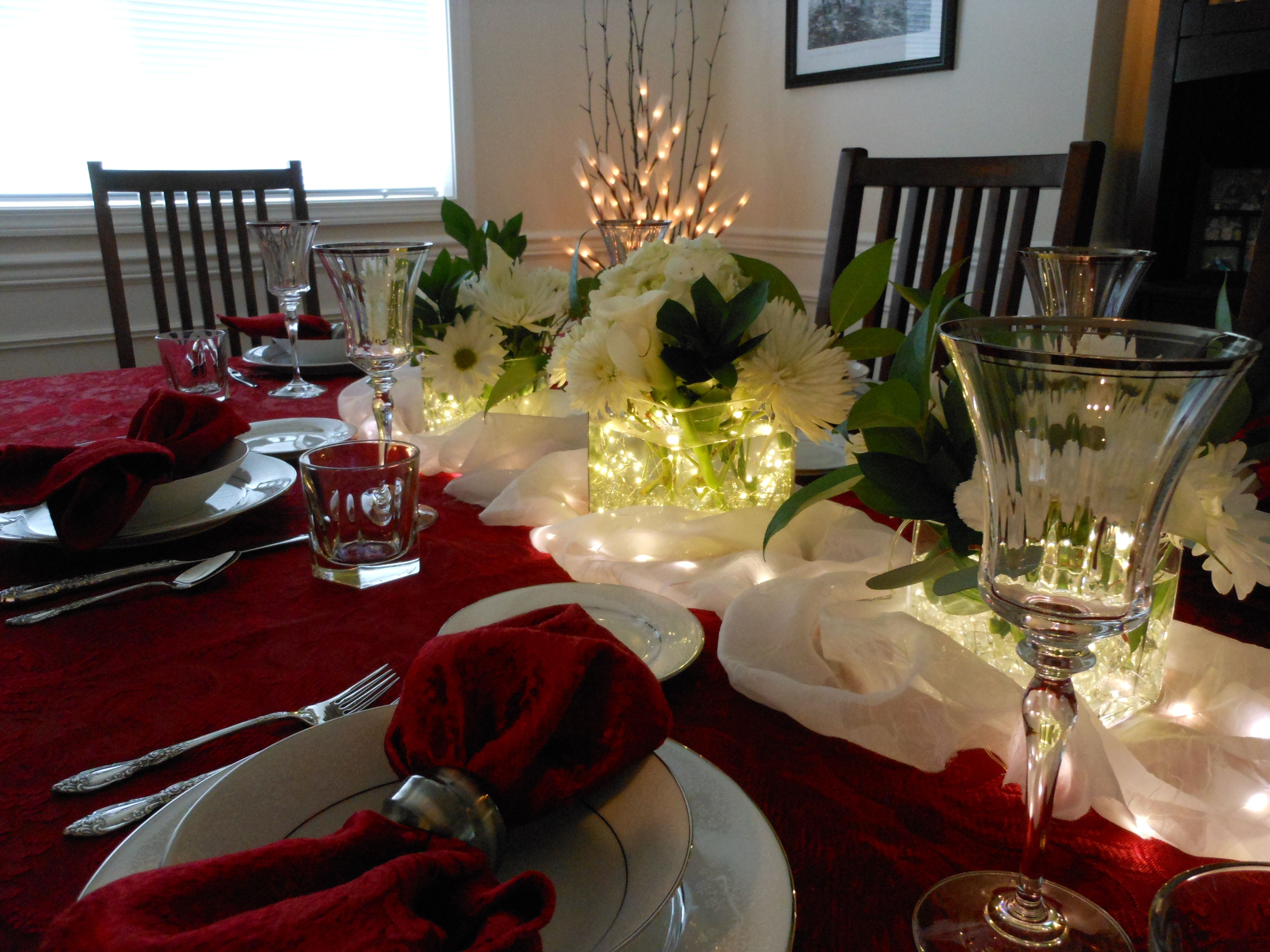 Holiday Table Setting Vases filled with fairy berry lights http