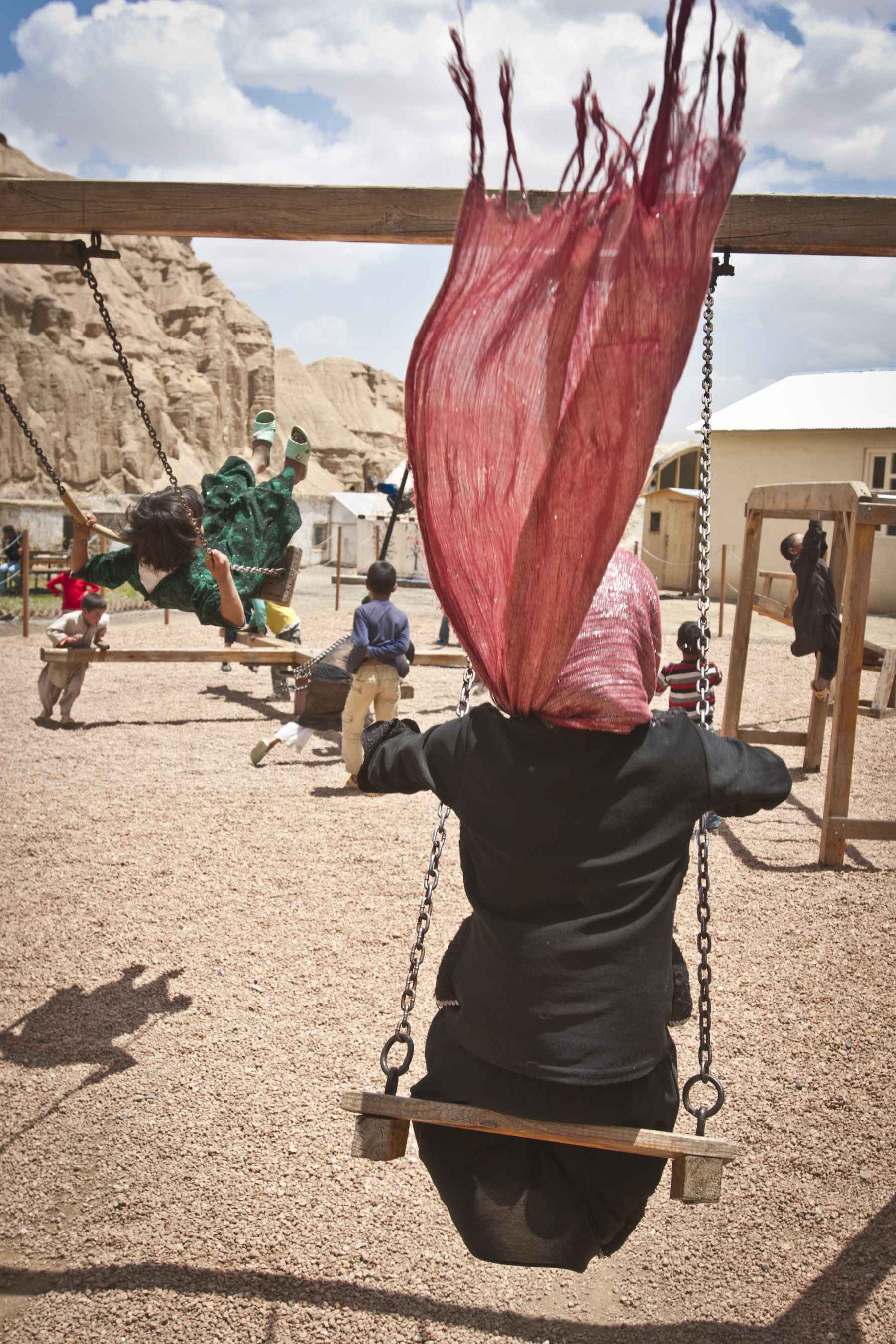 Two girls play on a swing set at the ARZU STUDIO HOPE community garden and playground in Bamyan, June 20, 2012. #afghanistan PHOTO CREDIT: Sgt. Ken Scar, 7th Mobile Public Affairs Detachment