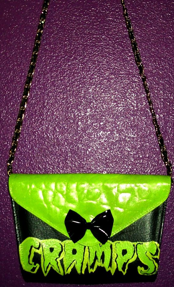All hand-painted leather Cramps envelope purse. Perfect for any creepy cute ghoul! This is also a one of a kind piece, done with neon green and yellow acrylic paint. Added a cute black PVC bow on the front flap. Comes with gold/leather chain.