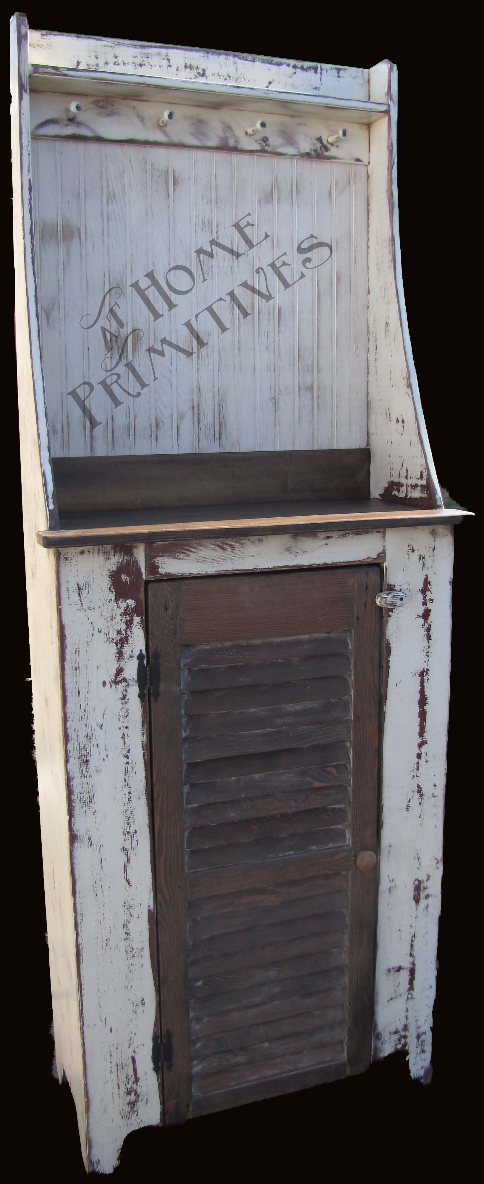 This two-toned (red under white) old looking thing was built brand new and heavily distressed.  The door however is an old wood shutter.  We call this our What-Not Cabinet!  by At Home Primitives