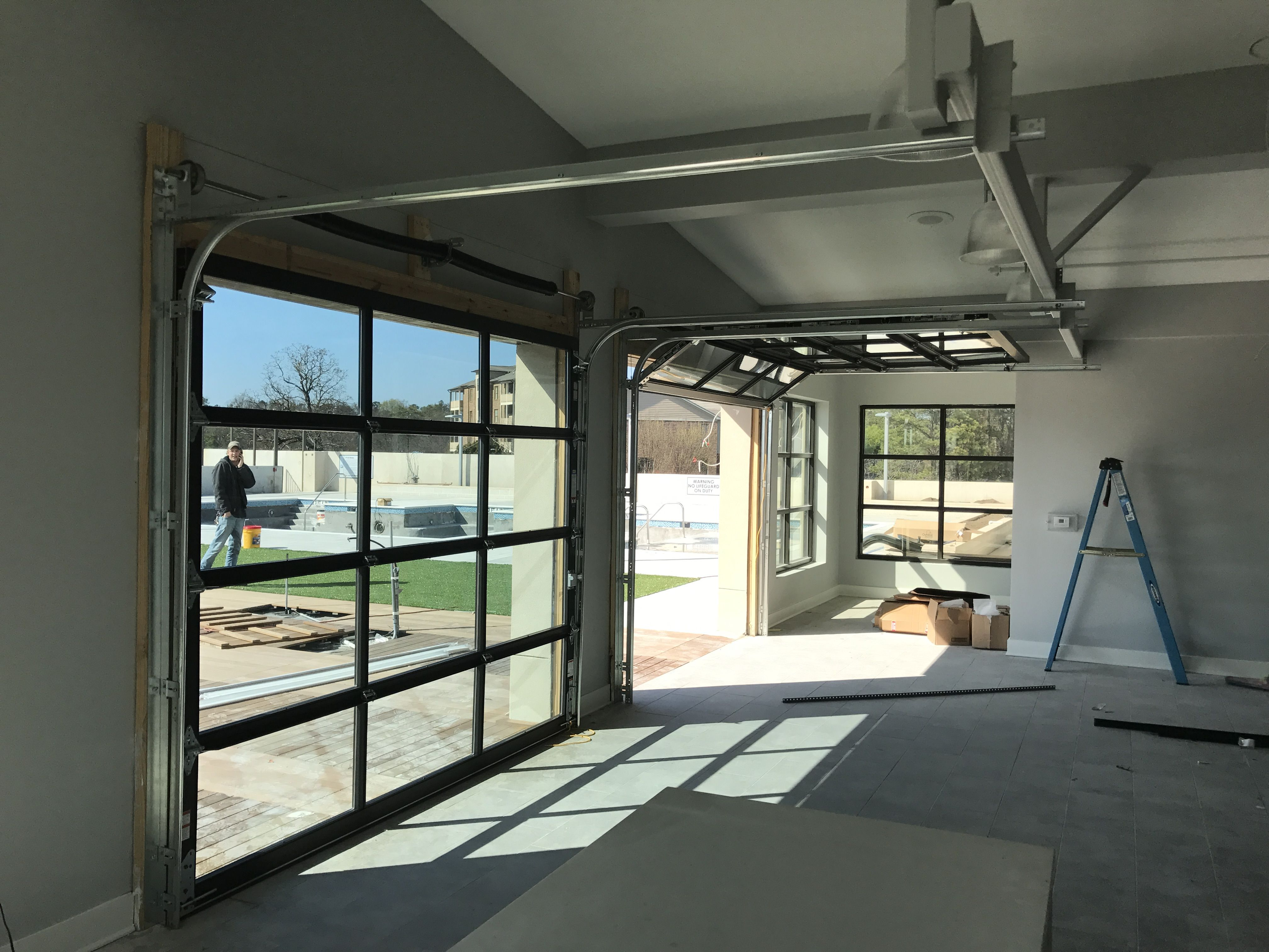 full view glass garage door separating game room from outdoor living and pool