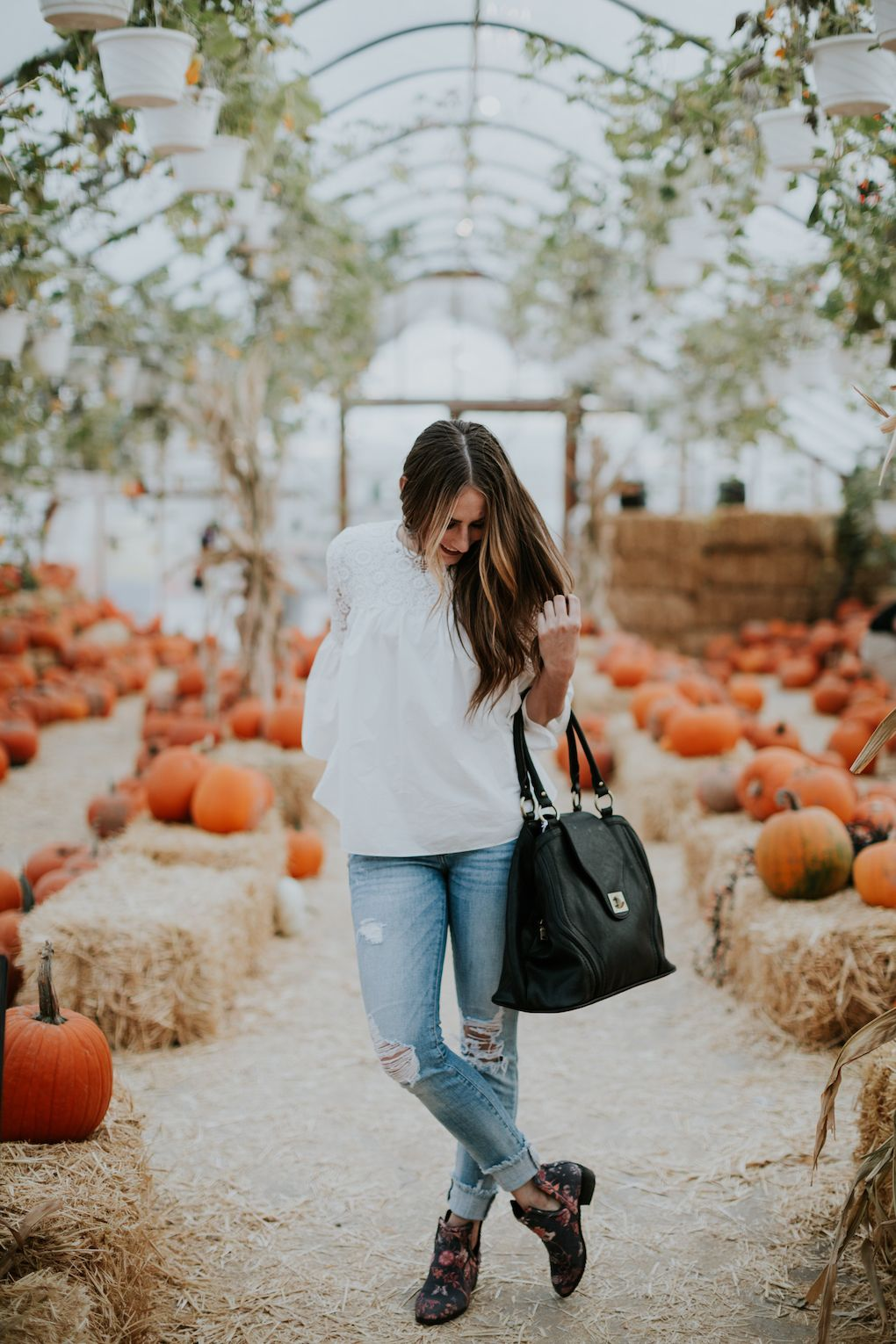 cdb182f529 girl wearing white lace top with distressed denim and brown booties  standing in a pumpkin patch