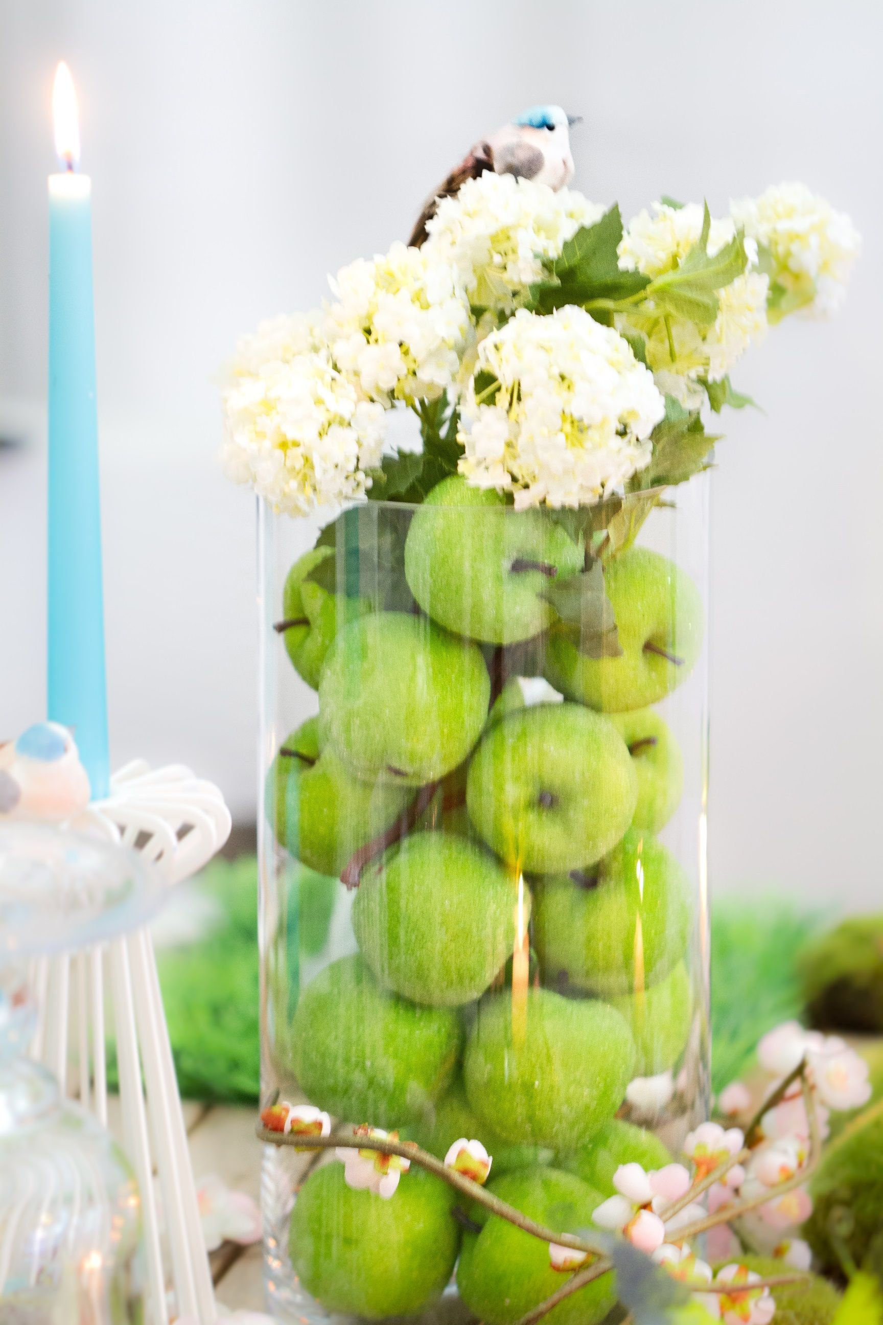 Table centerpiece with green apples and mimosa in a vase, and a ...