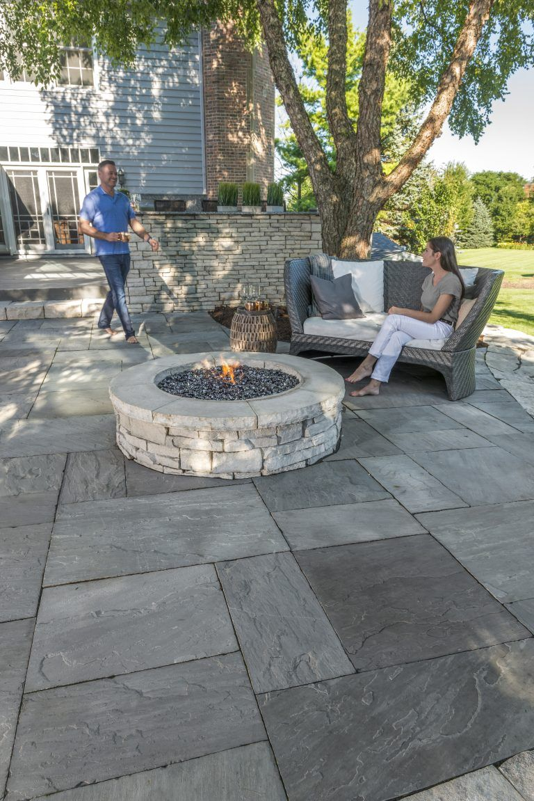 Couple Enyoing Their Rivercrest Wall Firepit Kit And Natural Stone Patio Photos Patio Pavers Design Stone Patio Designs Patio Stones