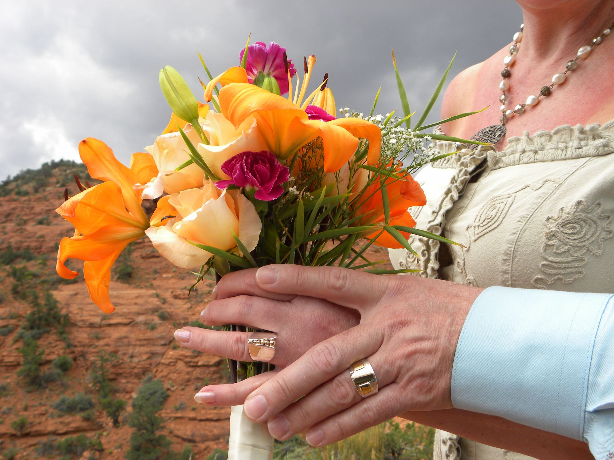 A women holds a bouquet of flowers at one of the popular Sedona weddings red rock locations.....  Give us chance to make your marriage ceremony memorable. #sedonadestinationweddings