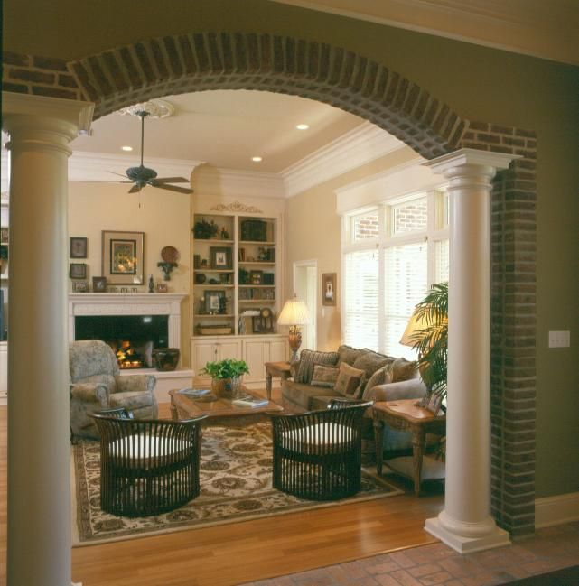 Tuscan Living Room With White Mantle And Built In Bookshelves Columns Going Into