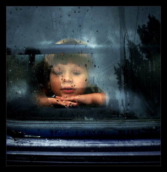 a little boy looking through the window of the bus