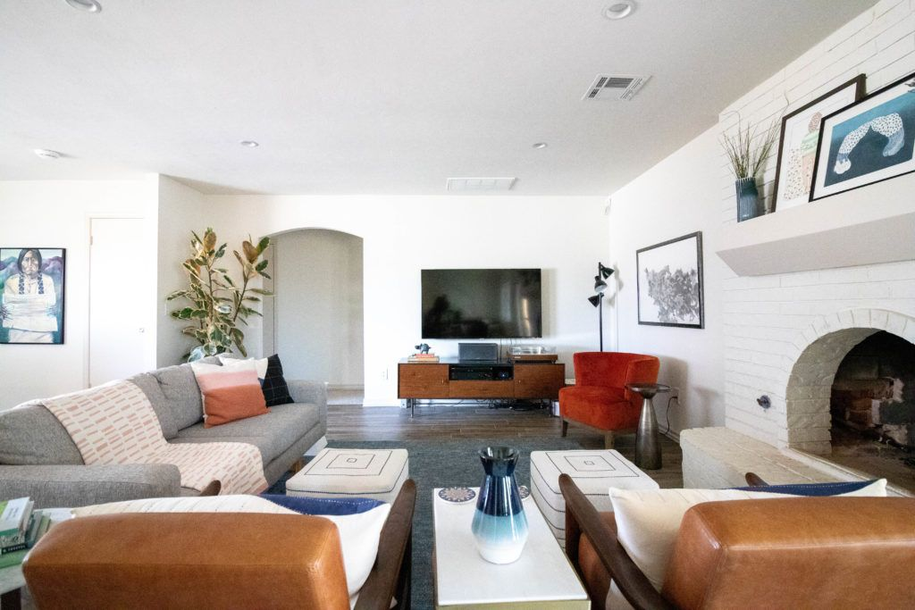 This Oklahoma City Mid Century Modern Living Room Features A Painted Fireplace Grey Sofa Leather Chairs And Fun Stylish Orange Chair