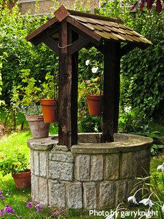 stone finish wishing well with dark wood cedar shingles with small flowerpots rustic wishing. Black Bedroom Furniture Sets. Home Design Ideas