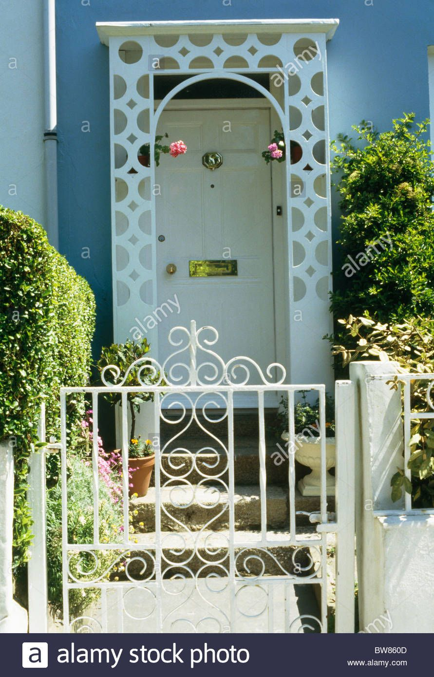 White Wrought Iron Gate In Front Of Small House With White Wooden