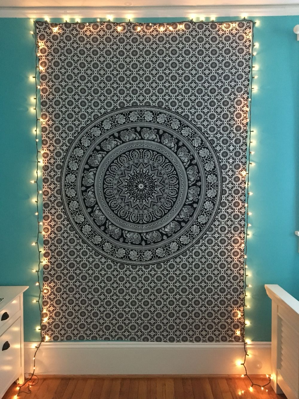 black and white wall tapestry with string lights around the border in turquoise room  bedroom