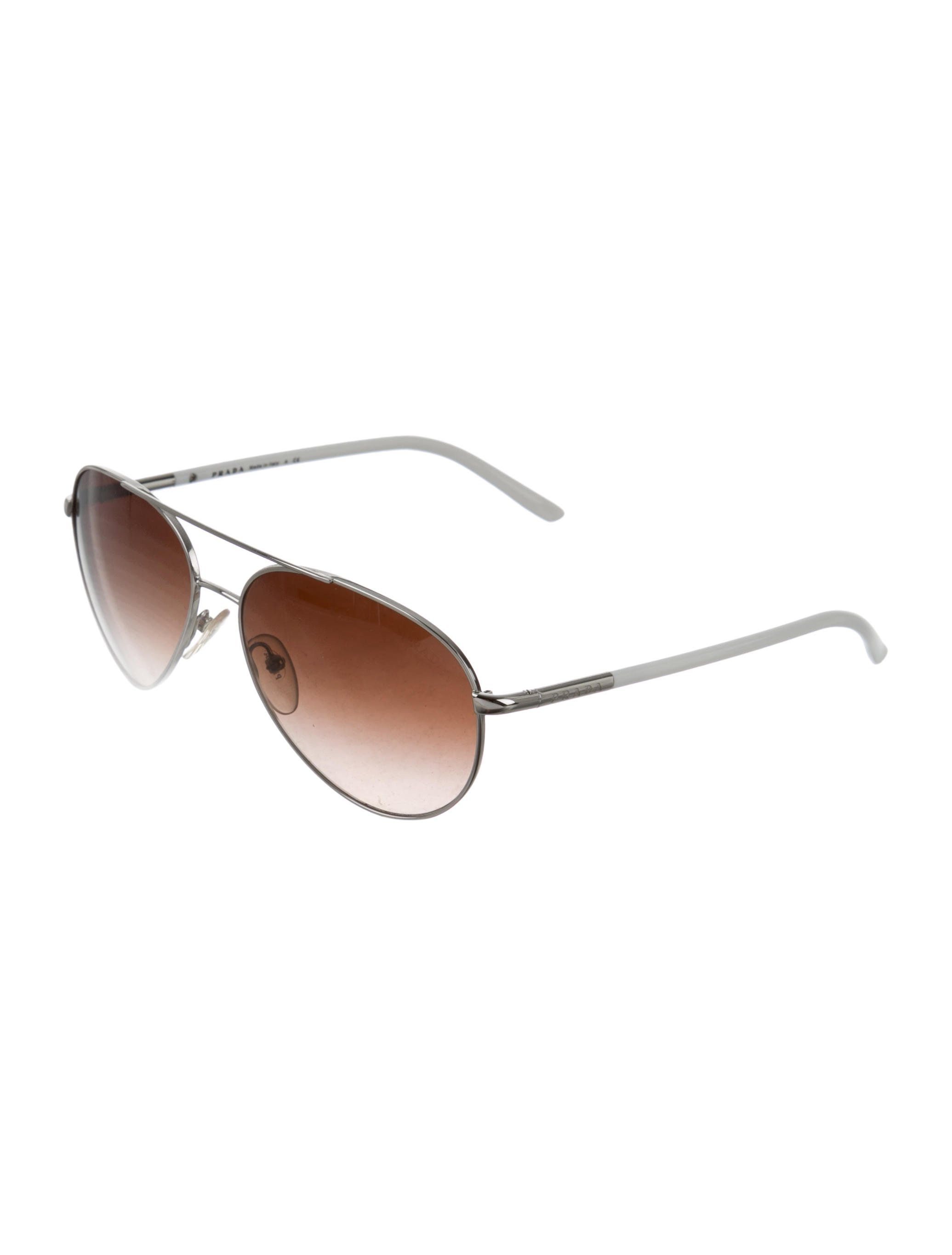 fc40e9f1540 Silver-tone metal Prada aviator sunglasses with tinted lenses and logos at  arms. Includes