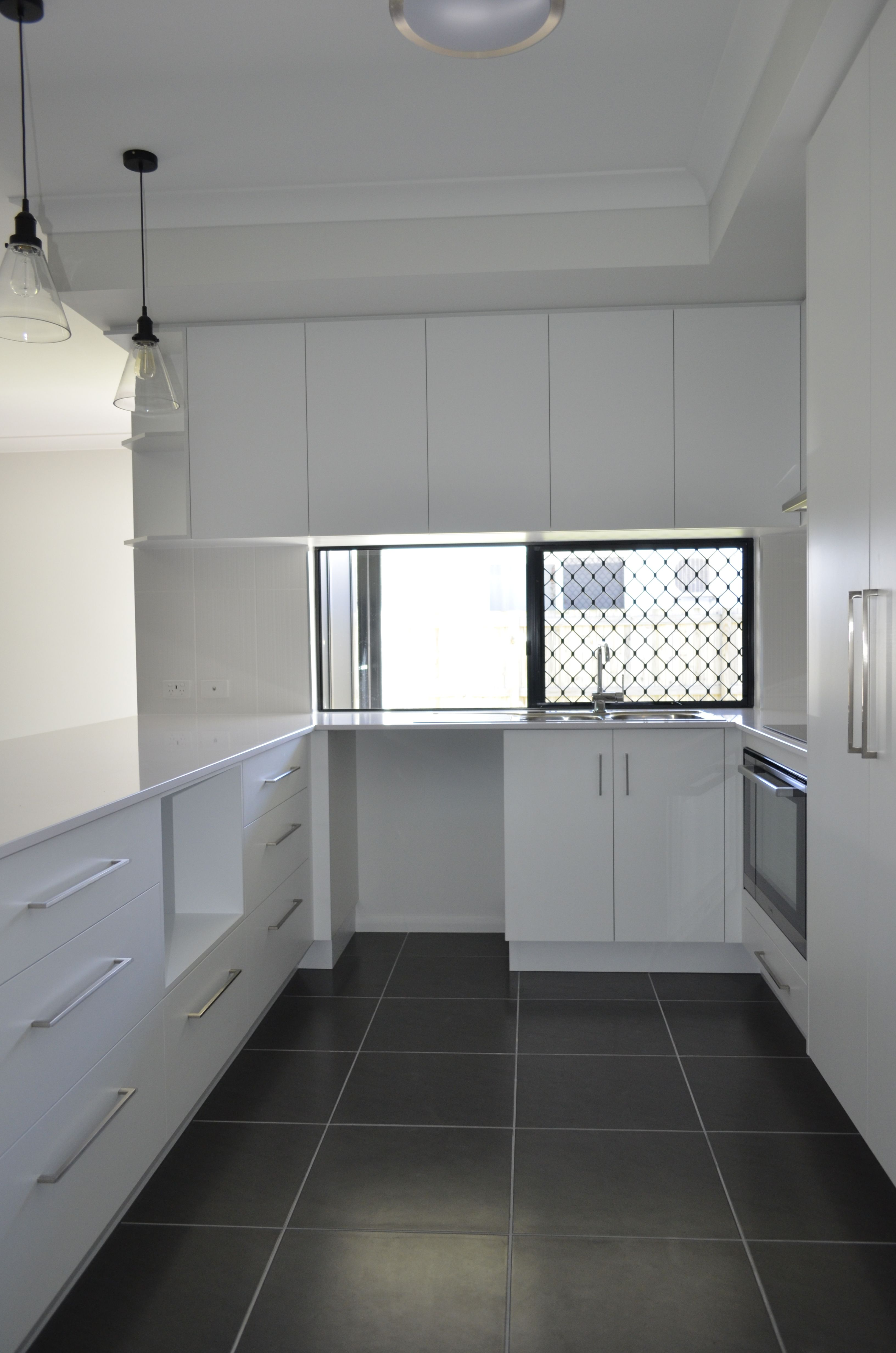 White On White U Shaped Kitchen Design With Window Stone Bench Top