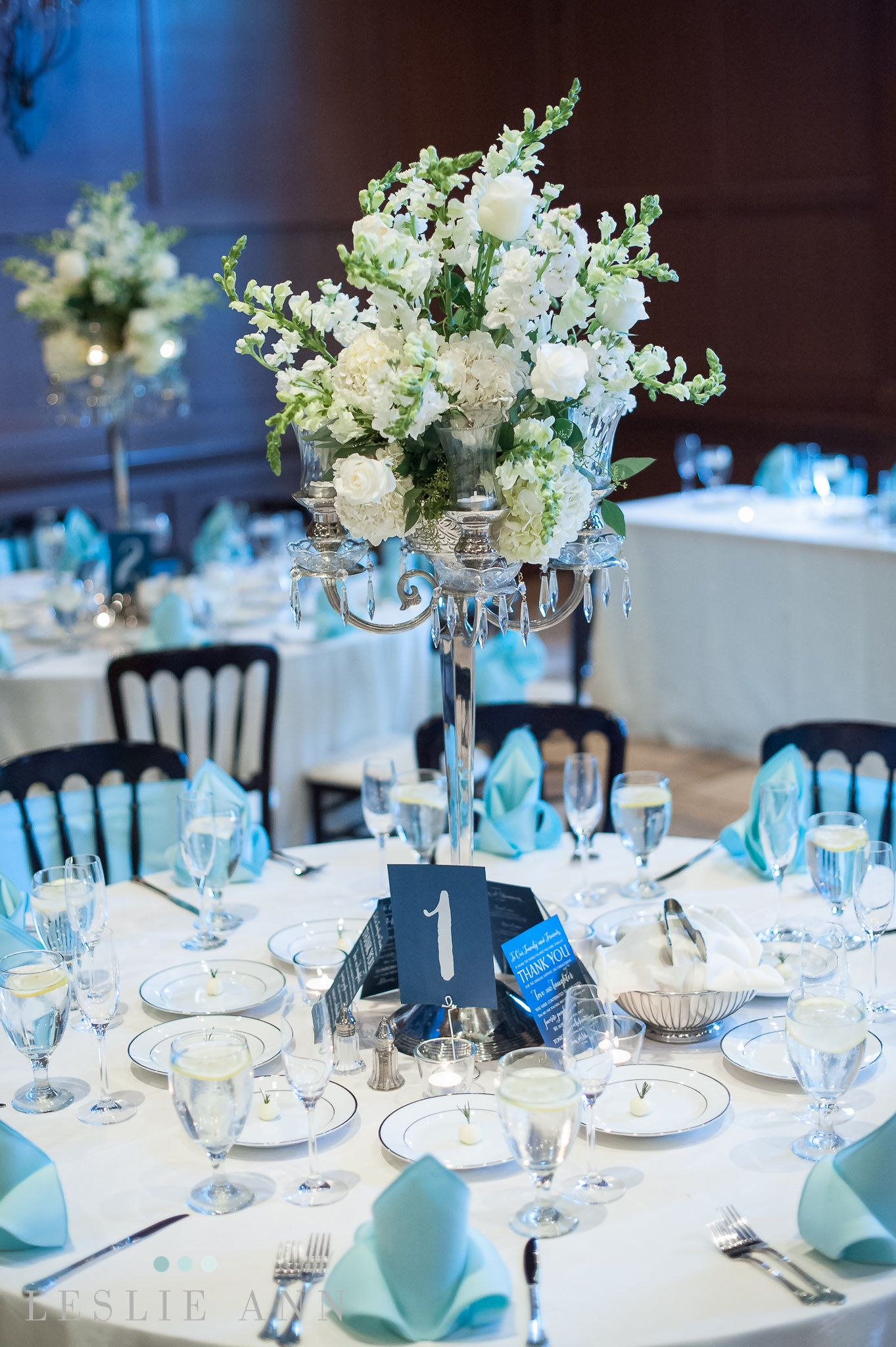 A tiffany blue and white table setting with high silver