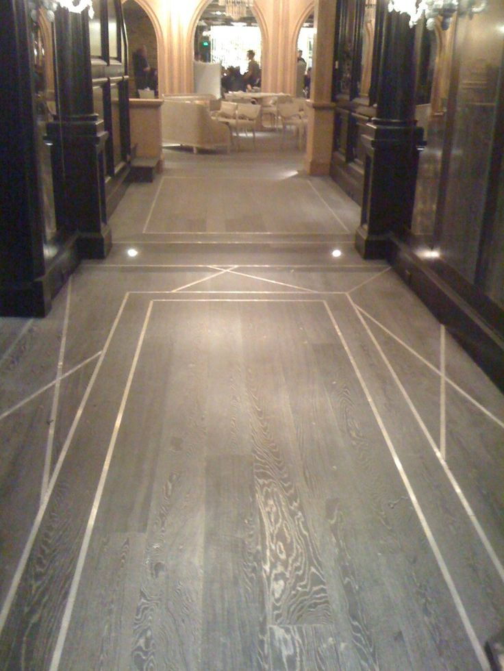 Use metal inlay to delineate foyer area in subtle way for Inlay flooring designs
