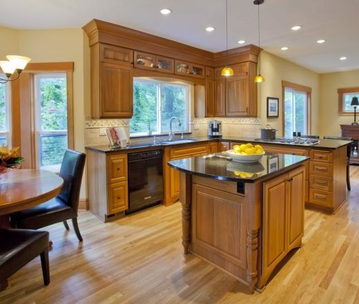 A Traditional Island Shaped Kitchen With Beech Wood Cabinets And Calming  Yellow Wall Accents.