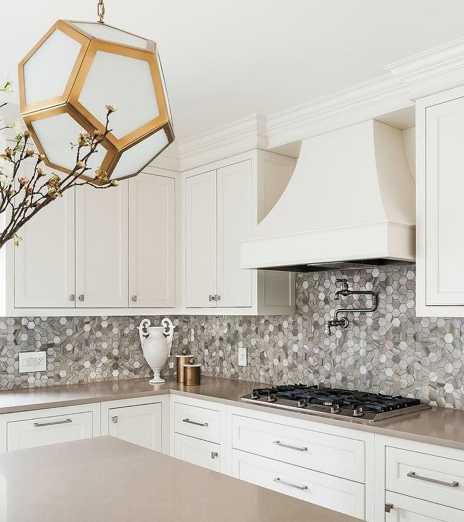 A Robert Abbey Pythagoras Pendant Hangs Above A Taupe Quartz Island Top Gray And White Kitchen Kitchen Backsplash Designs Interior Paint Colors For Living Room