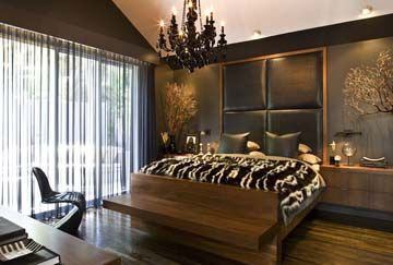 Leather headboard, built-in walnut furniture and a black crystal chandelier.
