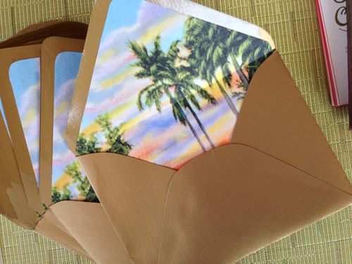The metallic gold envelope was lined with a vintage tropical sunset scene lending just a wink of tropical kitsch. By Shindig Bespoke, photo by Cor + Lux