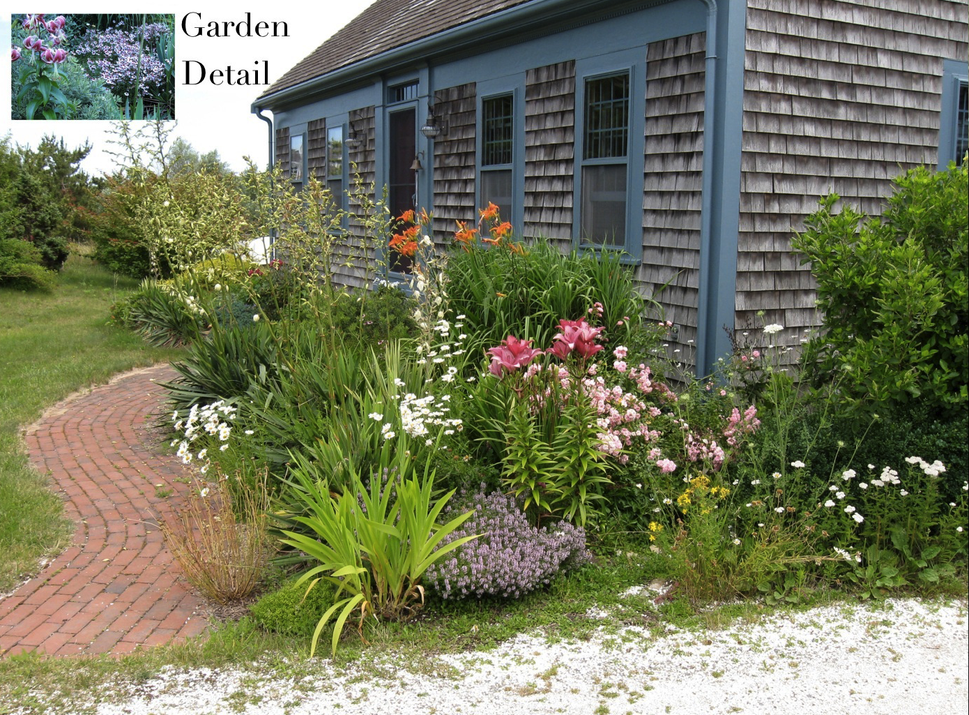 cottage garden design style rustic house with wood singles are combined with brick curvilinear path massed garden bed with lots of flower varieties