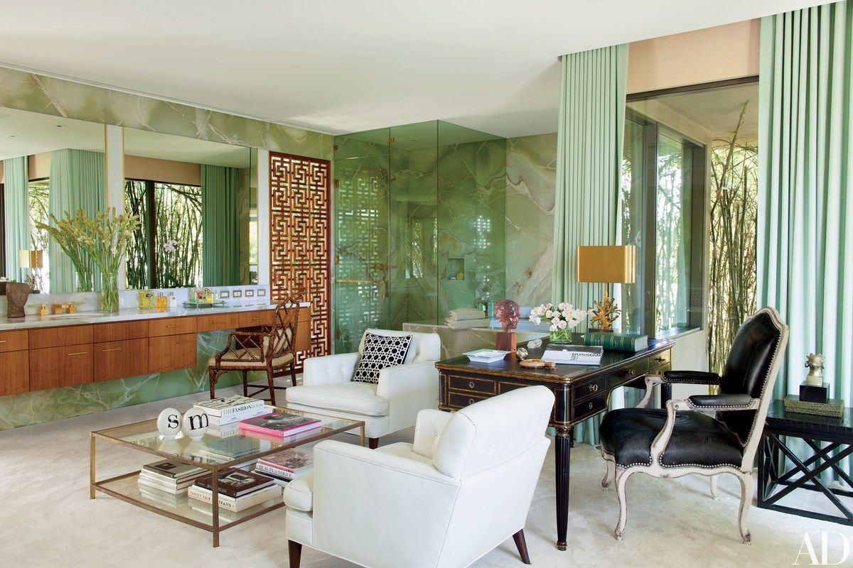 Meisel came up with the idea of the hybrid home office/master bath, which is sheathed in green onyx; the teak screen is by Dunning, and the cabinetry is by Marmol Radziner. The curtains are of a Jim Thompson silk, and a resin sculpture by Dorothy Draper is displayed on the vintage Jansen desk.