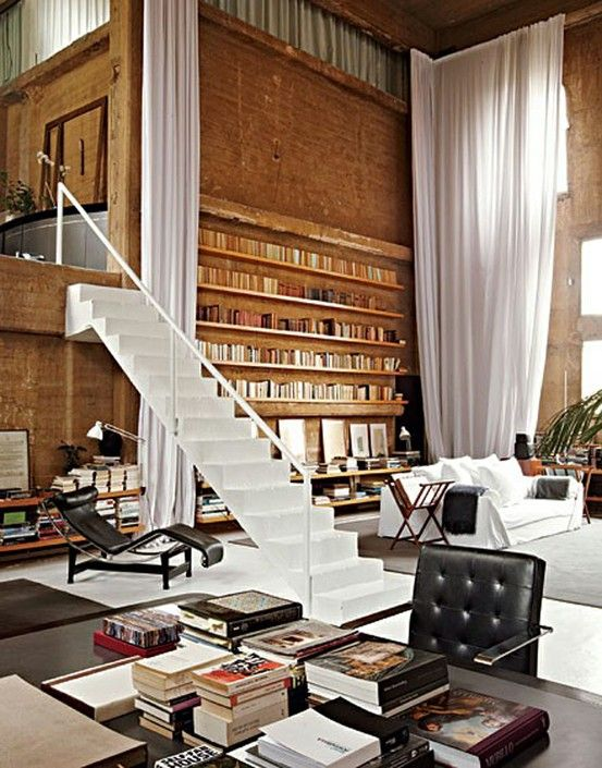 Large Living room with incredibly High library + minimal staircase