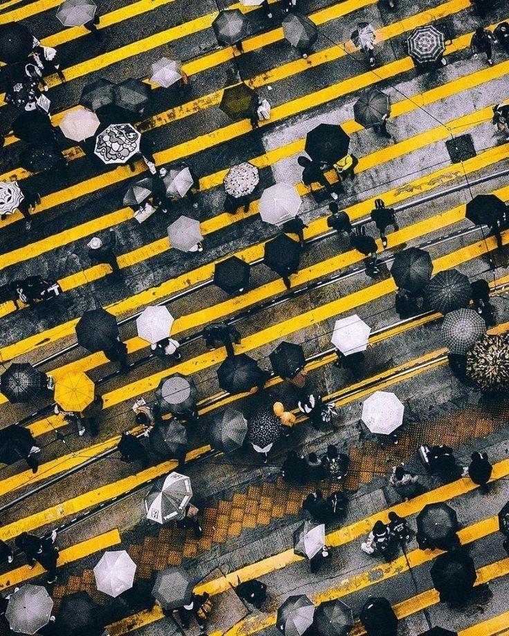 Landschaftsdrohnenfotografie: Auf den Straßen. Regentag in der Stadt. Schwarz und weiß. Regenschirme. Menschen. Eilen