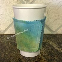"""This adorable and functional coffee """"cozy"""" is one of a kind!  Recycling the cardboard sleeve from a local coffee shop, it is sandwiched in between a piece of yellow and aqua over dyed denim and a solid yellow fabric.  Wraps around securely with Velcro.  Surely to let your friends know that yo..."""