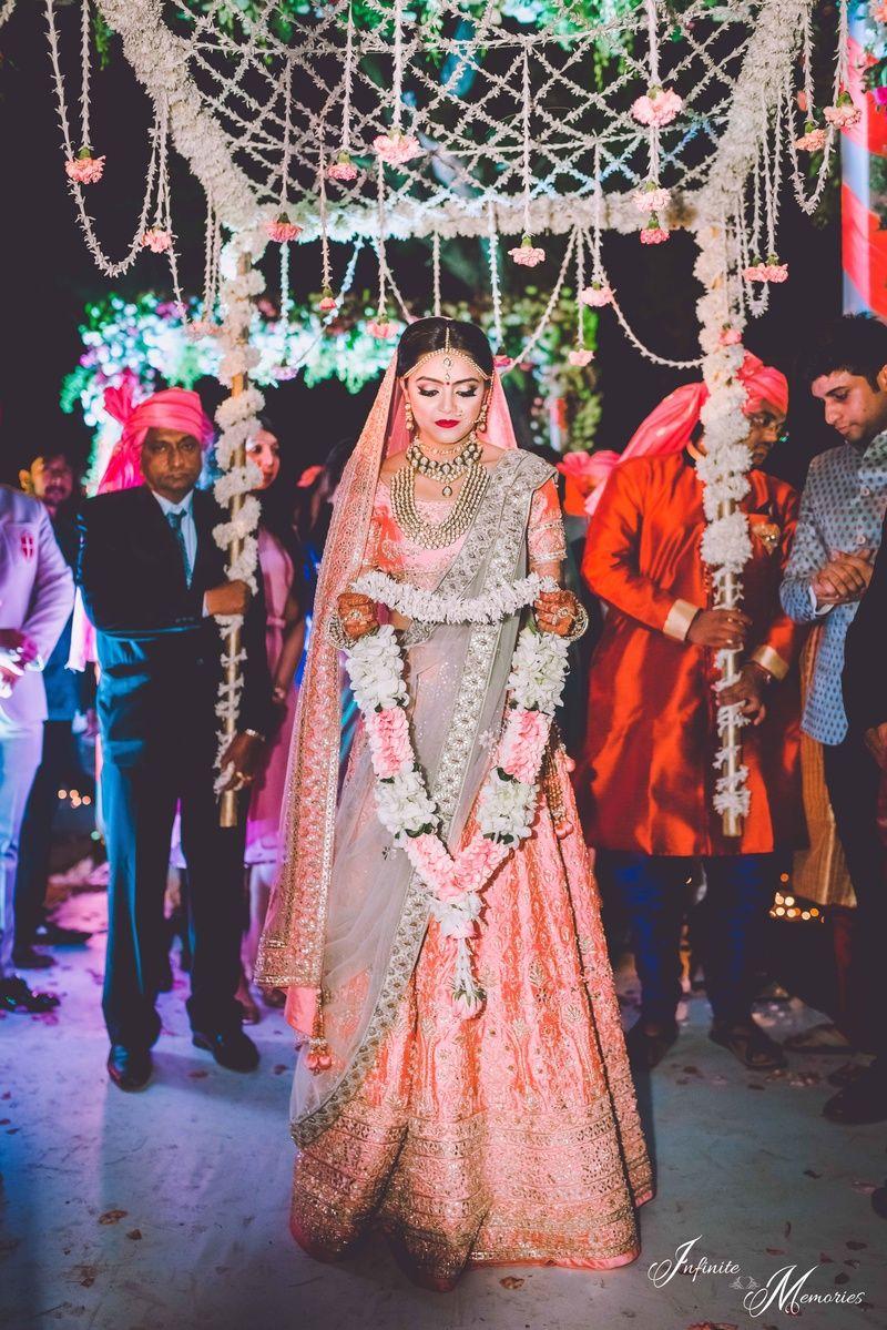 Bridal entry under phoolon ki chadar wearing peach and grey lehenga ...