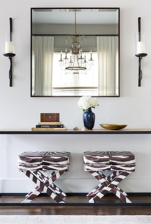 Superieur Two Zebra Print X Stools Sit Under A Long Simple Iron And Wood Console Table  Finished With A Light Stained Wood Top Positioned Beneath A Black Metal  Framed ...