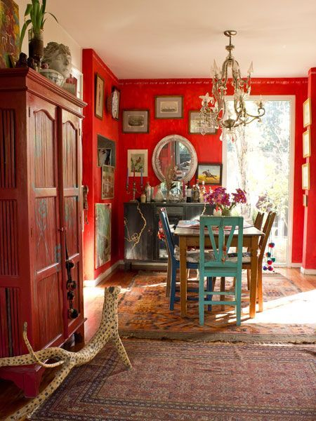 Red walls, artwork, brightly painted chairs, chandelier - Colorful home in Brazil. Casa Chaucha..: