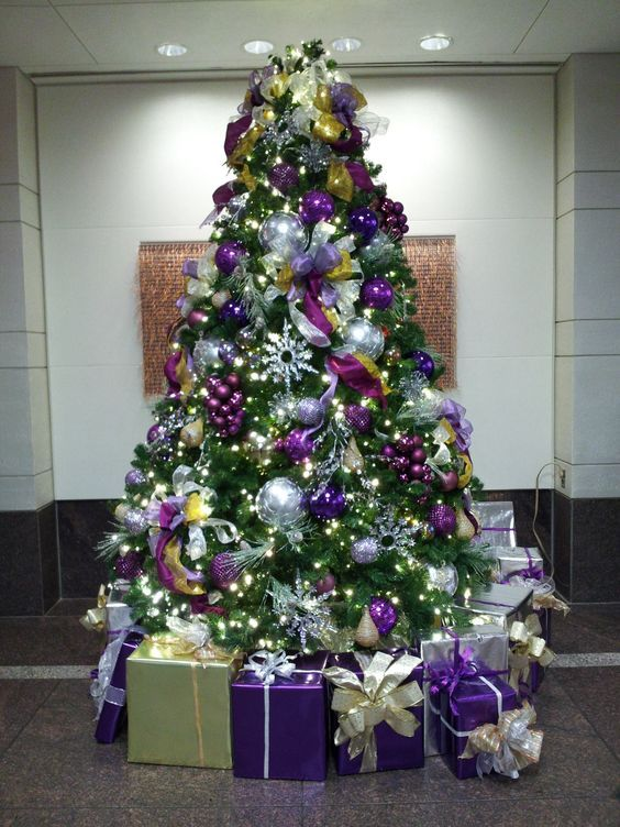 beautiful tree loaded with purple decorations and purple and gold wrapped gifts to finish the look