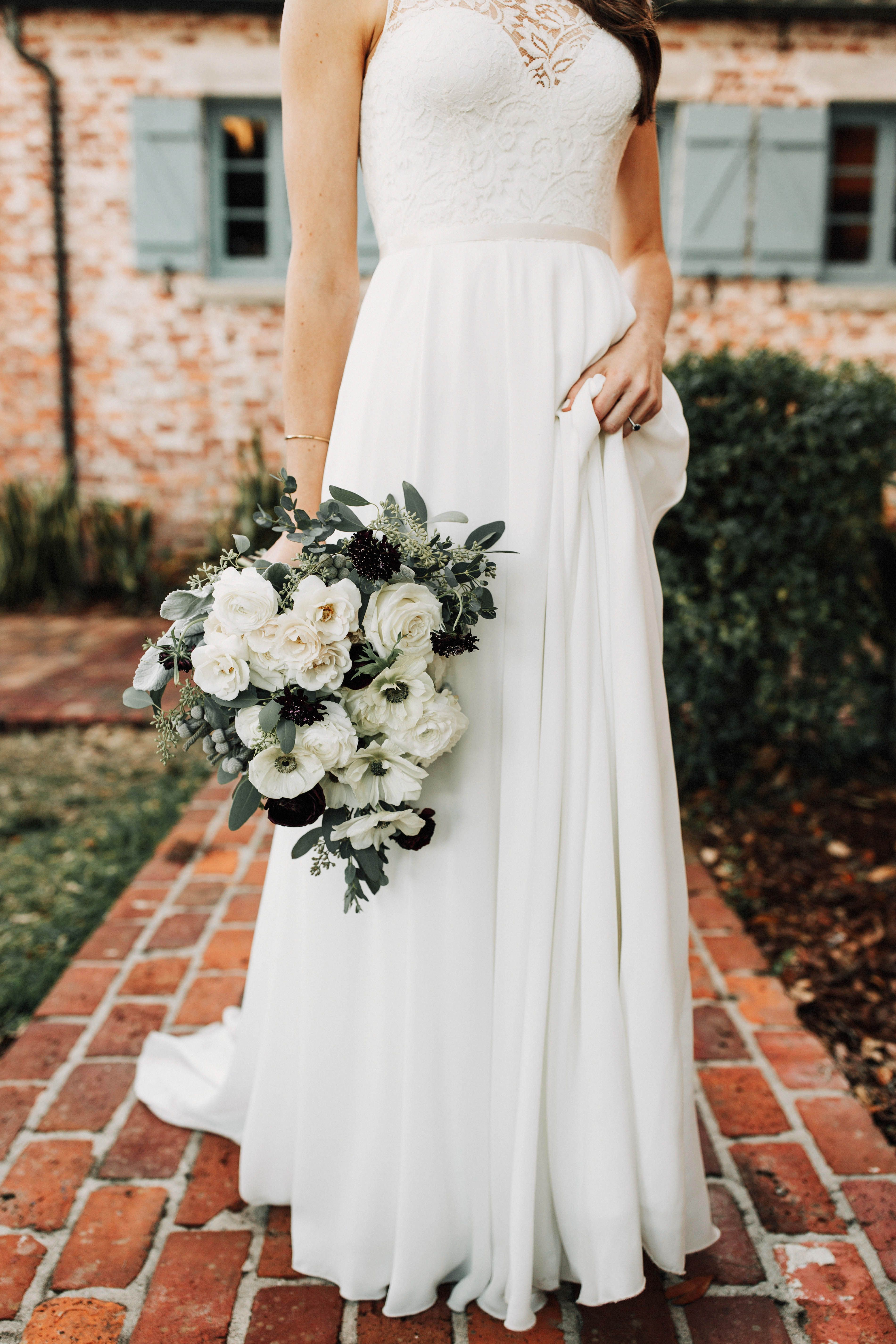 A Bride In Her Lace Gown Holds Her Loose Bridal Bouquet Of White