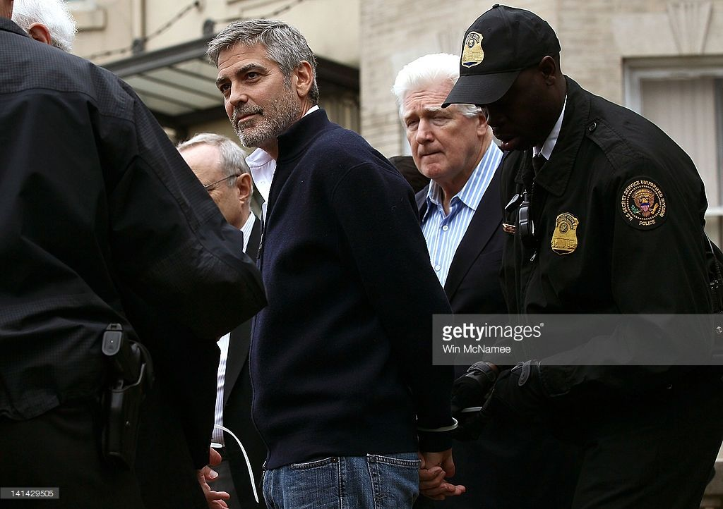 Actor George Clooney (L) is arrested with his father Nick Clooney (2R) during a demonstration outside the Embassy of Sudan March 16, 2012 in Washington, DC. United to End Genocide, the Enough Campaign and Amnesty International held a rally to call on the United States and world leaders to stop the violence in South Sudan and prevent hundreds of thousands of people from starving.