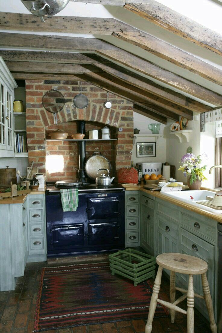 Cute Old Farm Kitchen Slanty Beamed Ceilings Brick Fireplace Surround For Vintage Stove Lots Of Cubbies And Drawers Wood Floors Butcher Block