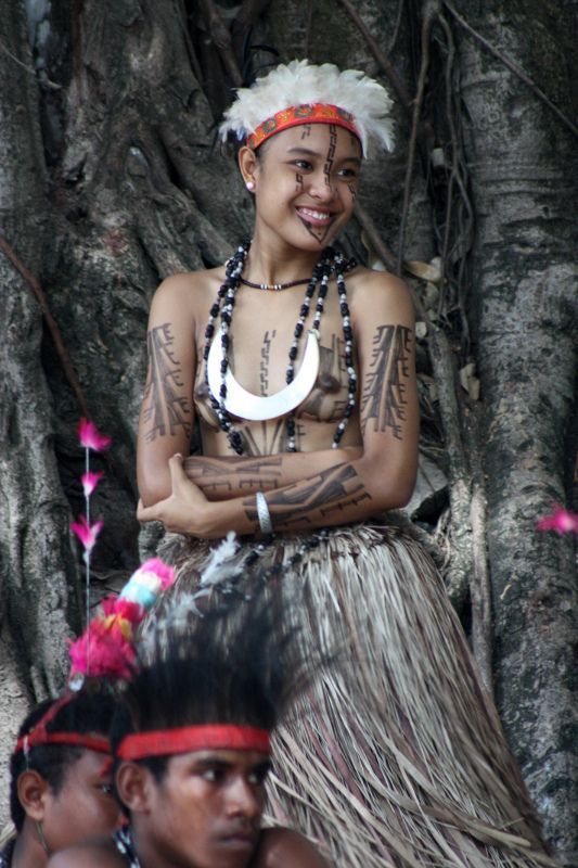 """71af7c134be0 Port Moresby, Papua New Guinea: A young woman dances during a traditional  """"sing sing"""" displayed at a local market."""