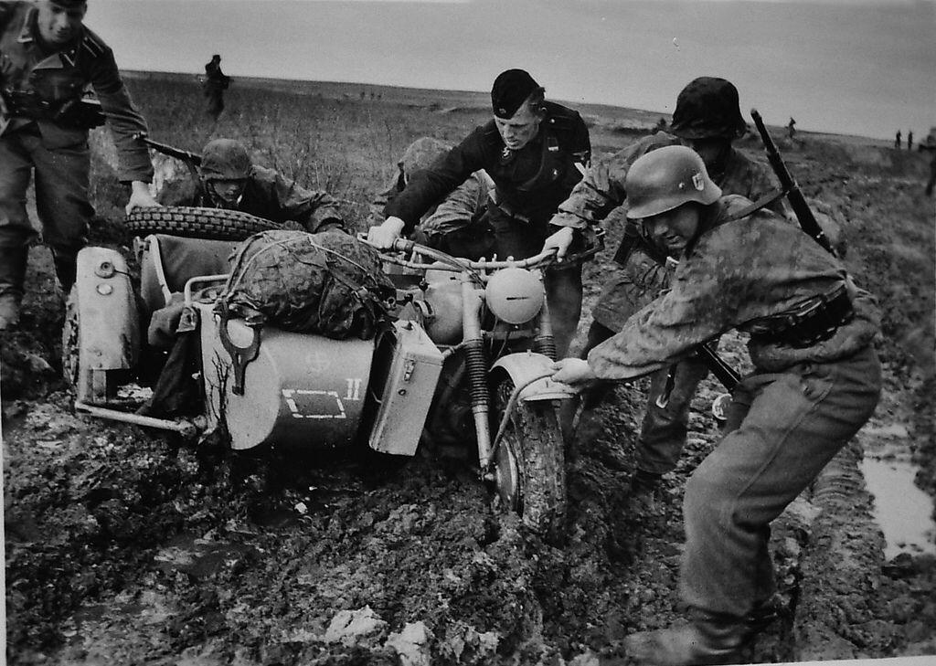 "Des Waffen-SS de la 5e SS Panzer Division ""Wiking"" tirent un sidecar dans la boue. En noir, un SS-Rottenführer, à gauche un SS-Unterscharführer"