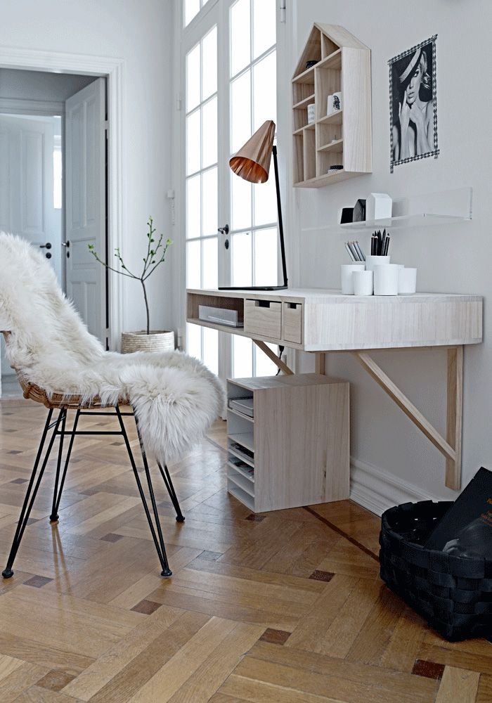 une peau de mouton sur la chaise le detail design de la mode scandinave le parquet les murs blancs et les meubles en bois sont les caracteristiques de