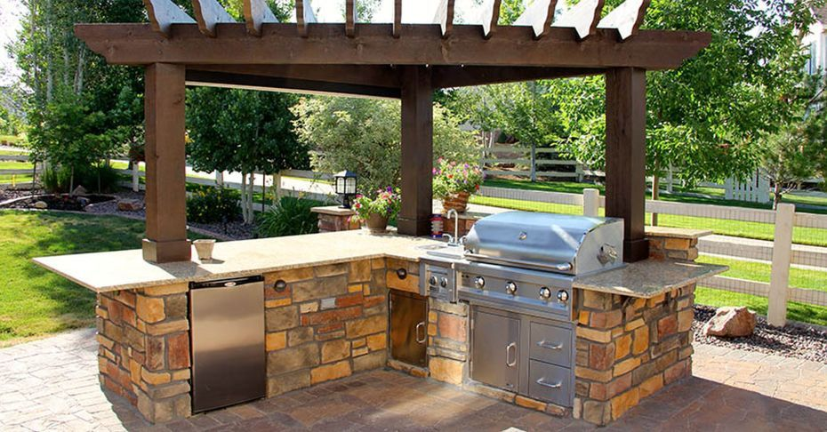Outdoor Kitchens Houston And L Shaped Design Under Brown Wooden Patio Pergola With Stainless Steel Grills Surrounded At Stone Panel Combined Light Tone