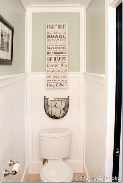 Half bath with DIY plank walls, wrapped in molding, DIY inlaid tile rug, black vanity and pocket door: