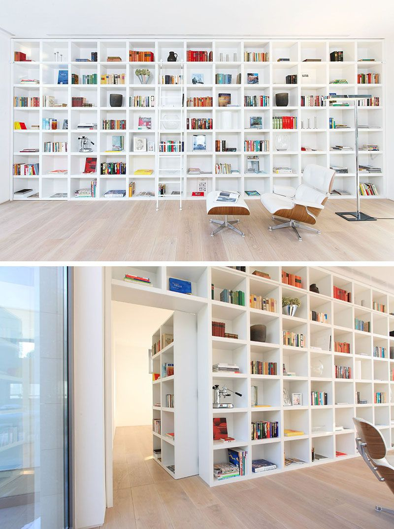 When its closed this secret door blends in completely with the other shelving units in this large wall of white bookshelves