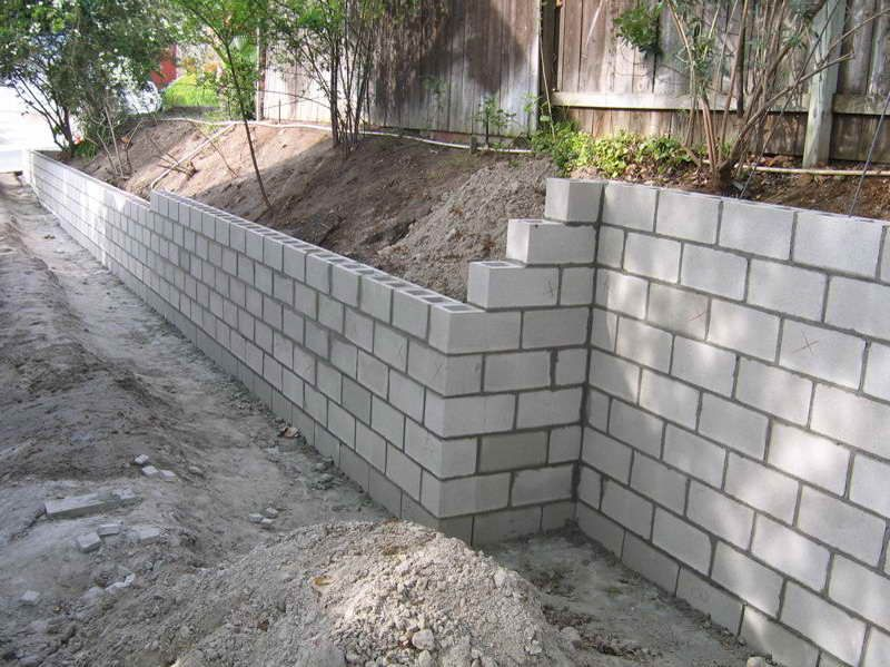 Cinder block retaining wall leave it plain so the kids can make murals with sidewalk chalk on - How to build a garage cheaply steps ...