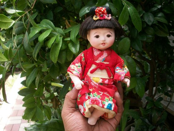 1940s Japanese Vintage Small Girl Ichimatsu Gofun Doll. This cute Japanese doll is made of shining white skin lacquer called gofun made from ground oystershell and glue. The joints on the shoulder, legs and head are not fixed to enable parts movement in direction you want. These said parts are joined together with a thread or string from the inside. The lacquered surface is in good vintage condition. no chips or nicks but it has a natural minute crack on the left leg due to age of the doll…