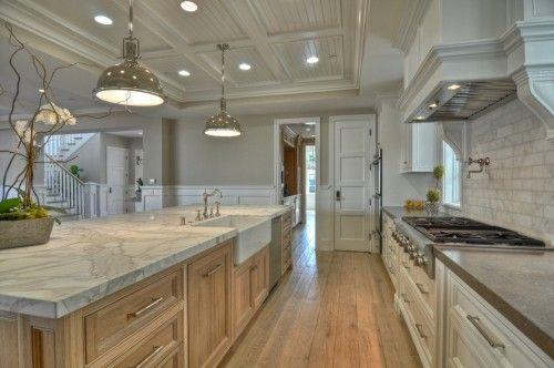 Interesting mix of formal marble counters and backsplash with trim, and casual light coloured floors and cabinets.