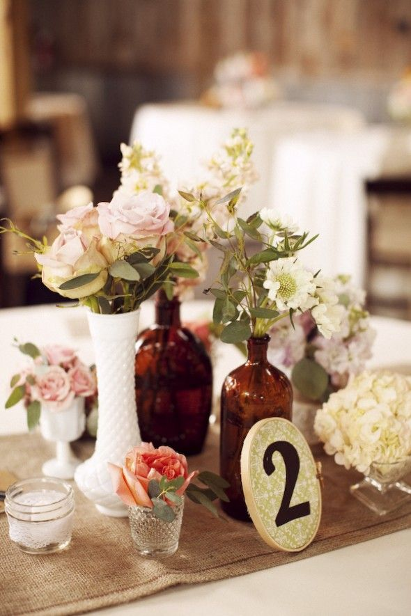 Country / Rustic Chic Wedding: Table centerpiece....clusters of mismatched bottles and small vases with flowers.