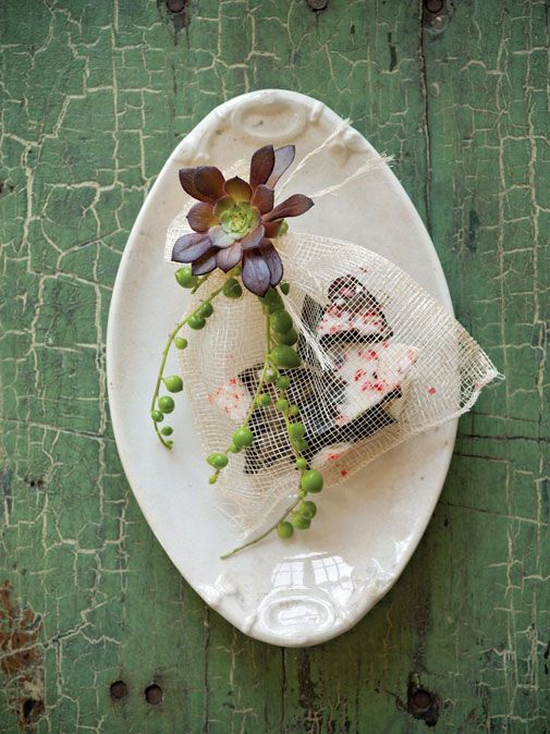 Sweet, simple, and stylish:  chocolate favor bag with raffia tie, purple Aeonium arboreum and trailing green pearl sedum on an antique plate.
