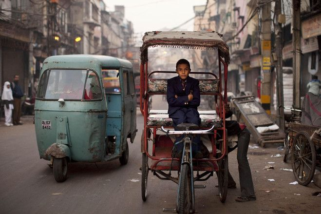 """An Indian boy in school uniform waited for a rickshaw driver to make an adjustment on a cool morning in New Delhi last December."". Getting Around Town - WSJ.com #rickshaw"