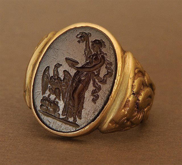 A seal ring, 20th century, streak tests at 14K yellow gold, set with an intaglio (sardonyx or glass paste), 18th or 19th century, bearing a scene of Hebe (Juventas), cupbearer to the gods of Olympus, pouring nectar to Zeus/Jupiter, represented by the eagle.