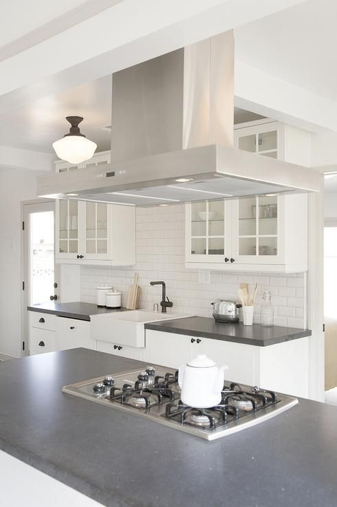 Black and white kitchen features a stainless steel vent hood placed ...