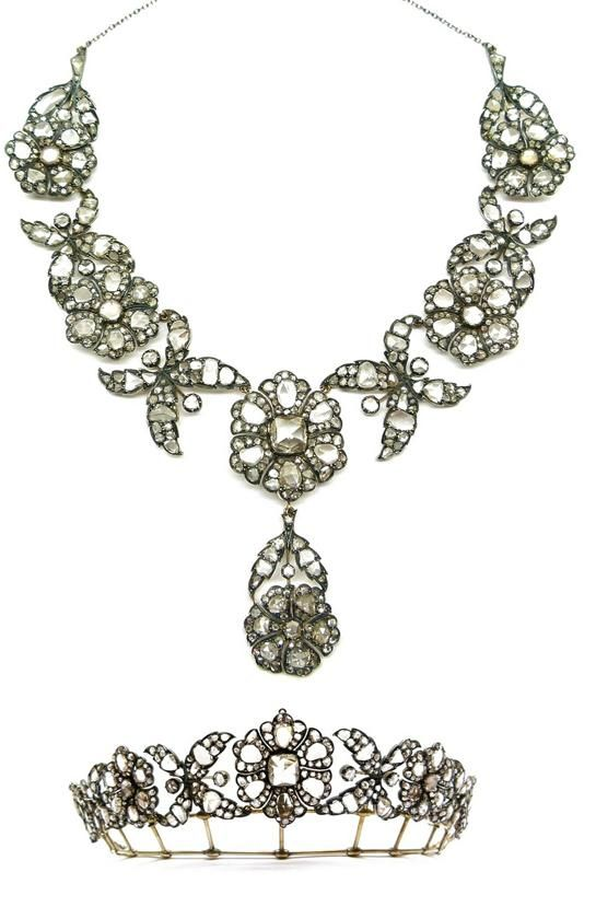 Any idea how they converted these? Mid-19th century rose cut diamond pendant necklace converting to a tiara, c.1860, with five graduated flowerheads, the principal one to centre with cushion rose stone to the middle and six cluster petals around, each flower alternating cross shape diamond foliate scroll, hung with a six petal flower and foliate stem pendant, open set in silver and gold, together with a tiara frame. S.J. Philips Ltd.